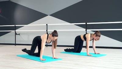 Women Training Buttocks on Mats in Hall