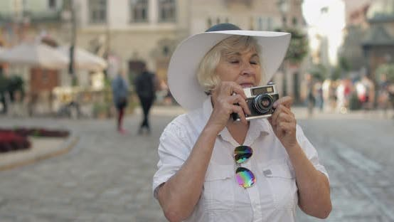 Thumbnail for Senior Female Tourist Exploring Town and Makes a Photo with Retro Photo Camera