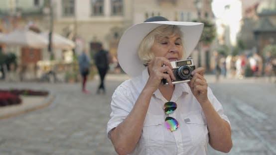 Thumbnail for Senior weibliche Tourist Erkundung der Stadt und macht ein Foto mit Retro-Fotokamera
