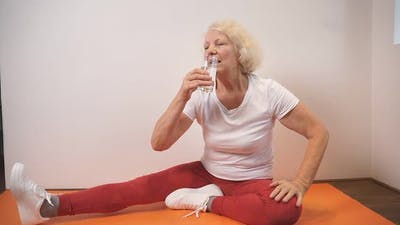 Woman in Sportswear Sits on a Fitness Mat and Drinks Water After Yoga and Fitness Classes at Home