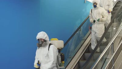Disinfection Service on Escalator in the Building Team of Sanitation Workers in Suit Using Pressure