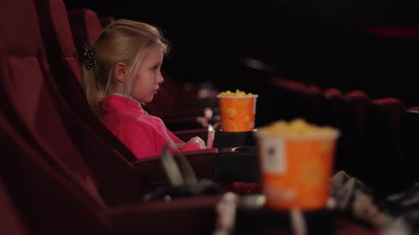 Little Girl Alone in the Cinema Looks at the Cinema Screen