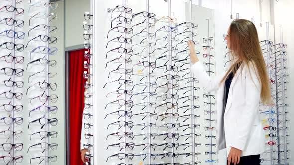 Thumbnail for Customer in eyeglasses store. View of woman choosing eyeglasses from rack