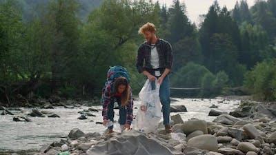 Volunteers Picking Plastic Bottles on River Shore