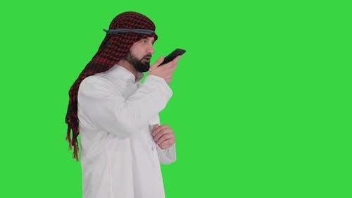 Arabian Businessman Recording Voice Message or Using Voice Digital Helper on a Green Screen, Chroma