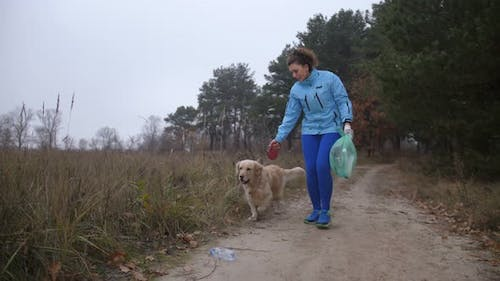 Female Jogger with Dog Doing Plogging in Woodland