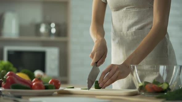 Cover Image for Woman Cutting Cucumber While Making Salad in Her Kitchen at Home Vegetables