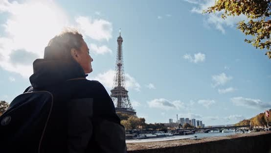 Thumbnail for Tourist Girl with Backpack Looking at Eiffel Tower and River Seine and Taking Photo on Smartphone