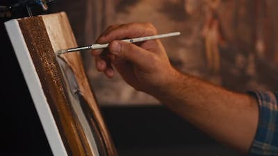 Man Artist Paints with Brush Strokes of Black Paint Oil