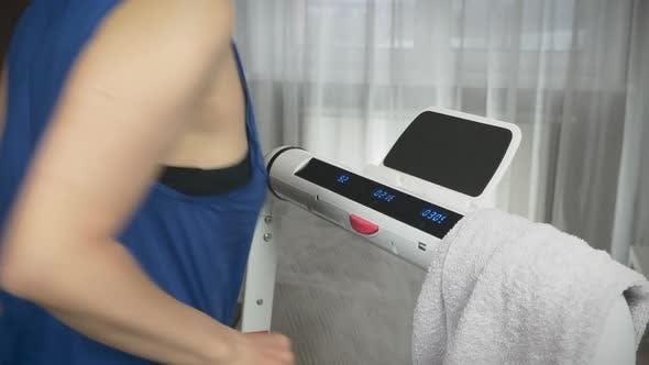 Overweight woman is running on treadmill