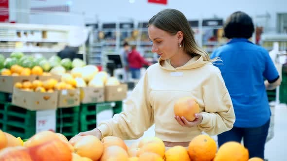 Woman Buying Fresh Citrus Fruits - Grapefruits at Supermarket. Health Care Concept