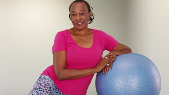 Thumbnail for An elderly back woman rests on a medicine ball while posing for a portrait