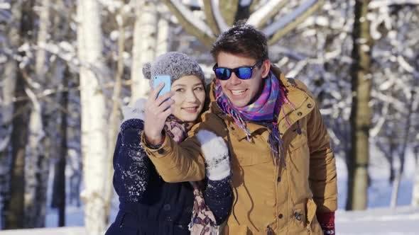 Thumbnail for Junges glückliches multikulturelles Paar, das Selfie in der Winterstraße nimmt. Urlaub, Weihnachten, Liebe, Familie