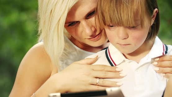 Thumbnail for Down Syndrome Boy Holding Tablet with Mother