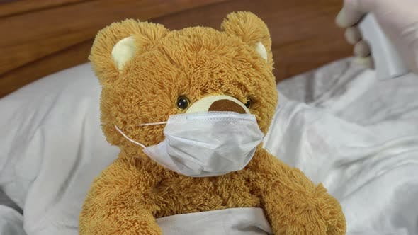 A Teddy Bear Is Measured with an Infrared Thermometer. The Doctor Makes a Temperature Measurement