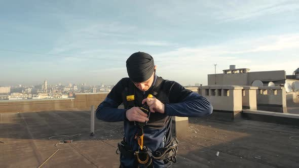 Thumbnail for Close-up Shot of a Male Industrial Climber Standing on a Roof Fastening Straps with Hooks and