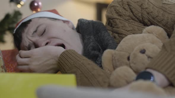 Closeup of Young Man Yawning and Sleeping with Teddy Bear with Decorated Christmas Tree at