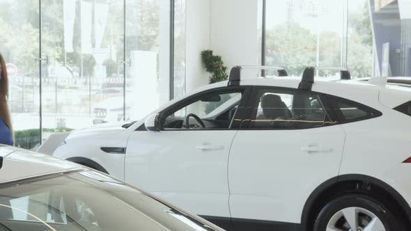 Thumbnail for Happy Female Customer Smiling To the Camera While Choosing New Car To Buy