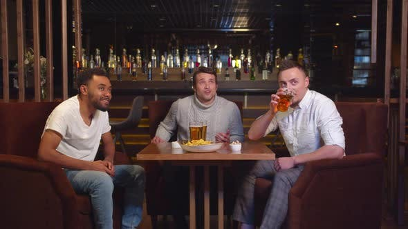 Thumbnail for Slow Motion, Friends Sit at the Bar, Drink Beer and Watch Footbal