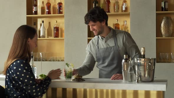 The Male Bartender Serves the Client a Mojito Cocktail and Communicates with the Customer
