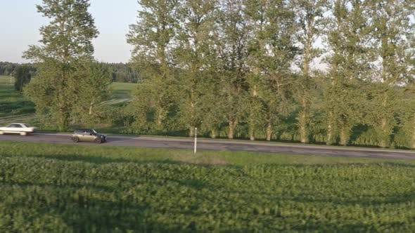 Aerial View of Grey Car Driving on Country Road. Side View Tracking Shot. .