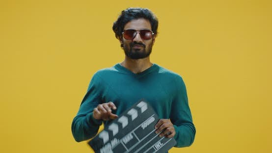 Thumbnail for Cheerful Man Clapping Clapperboard