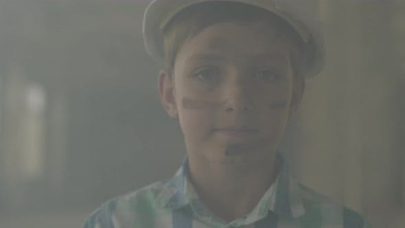 Thumbnail for Portrait Teen Boy in a Protective Helmet Looking at the Camera in the Background of Smoke Indoors
