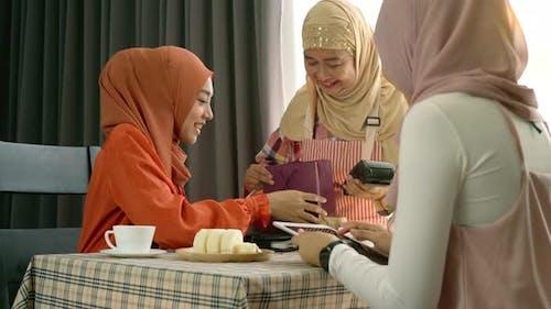 Asian Muslim Woman Using Mobile Phone Payment