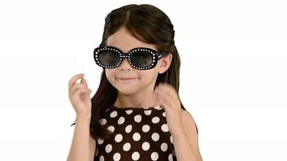 Darkhaired Little Girl in Polkadot-Kleid, das schwarze Sonnenbrillen anzieht und auf die Kamera verzichtet