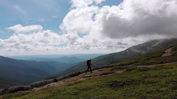 Thumbnail for Aerial View of a Traveler Photographer with Backpack Climbing By Mountain Range