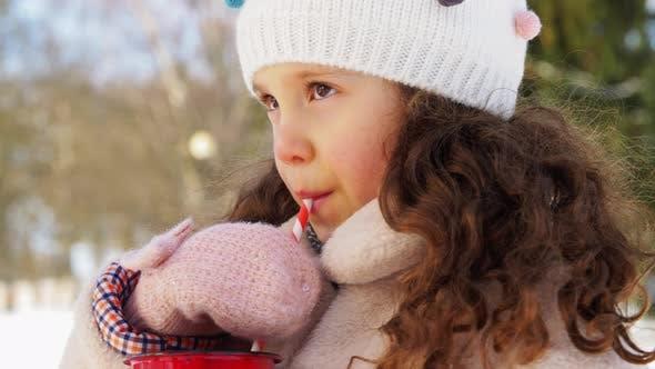 Thumbnail for Kleines Mädchen trinken heißen Tee im Winter Park