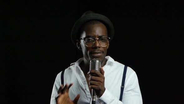 Thumbnail for Man Singer Sings Into a Microphone Dance and Snapping Fingers. Black Background. Close Up