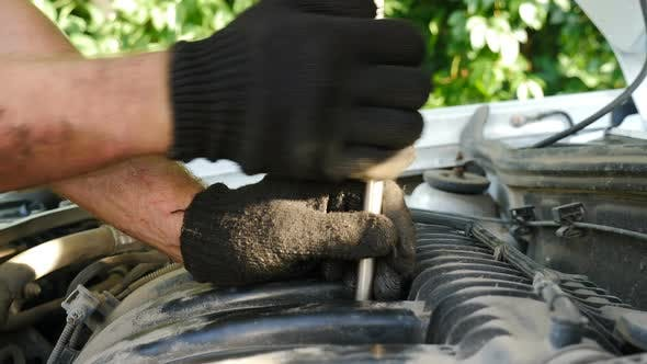 Auto Mechanics in Gloves Repairing Car at Service Station