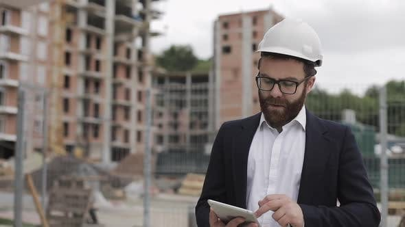 Thumbnail for Architect Man Wearing Business Suit Walking with Tablet on the Construction Site and Analyzing
