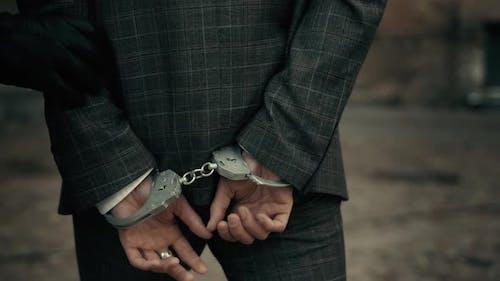 Die Polizei bringt den gefesselten Gefangenen mit Handschellen ins Gefängnis. Inhaftierung eines Verdächtigen. Hintere Ansicht