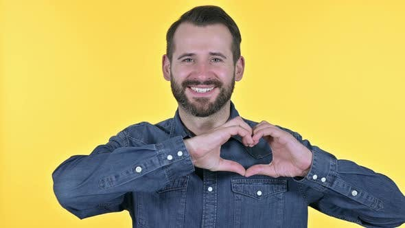 Thumbnail for Beard Young Man Making Heart Shape with Hand, Yellow Background