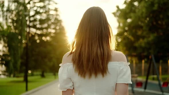 Thumbnail for Attractive Young Woman Turns Around and Looks at the Camera in the Sun Light