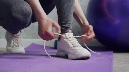 A Woman Ties Shoelaces on Sneakers