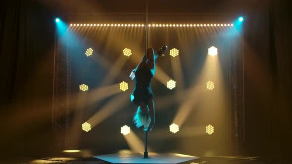 Thumbnail for Attractive Strip Dancer Performs Tricks on a Pole. Silhouette of a Sexy Blonde in Lingerie and High
