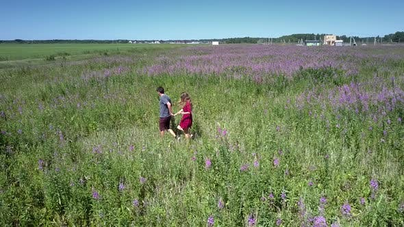 Pretty Couple Walks in Direction To Violet Blooming Plants