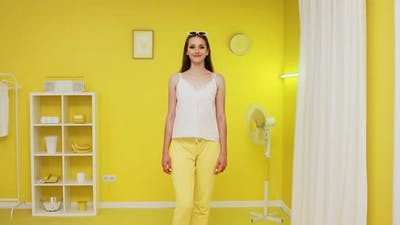 Portrait of Confident Woman Standing In Yellow Interior