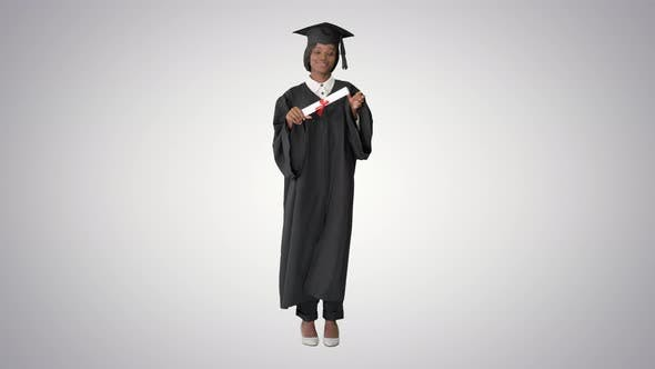 Cover Image for Happy Afro Graduating Female Student Dancing on Gradient Background
