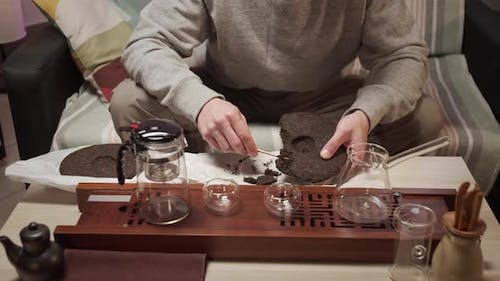 Traditional Eastern Chinese Tea Ceremony at Home. A Man Picks Pieces From a Tile of Compressed Black