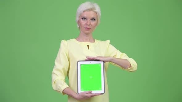 Thumbnail for Happy Beautiful Businesswoman with Short Blond Hair Showing Digital Tablet