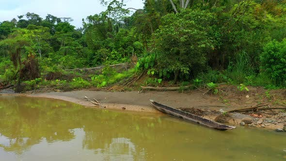 A traditional wooden canoe laying in a sand bank of a tropical river
