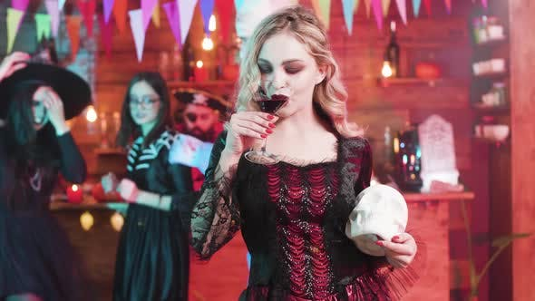 Thumbnail for Vampiress Fulfills Her Taste of Blood at a Halloween Party with a Skull in Her Hands