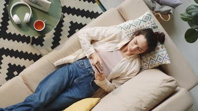 Woman Resting on Couch and Using Smartphone