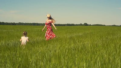 Slow Motion Young Mother Plays with Child in the Field Dressed in Red Dress That Flutters in the