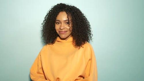 Smiling model in orange hoodie posing in studio