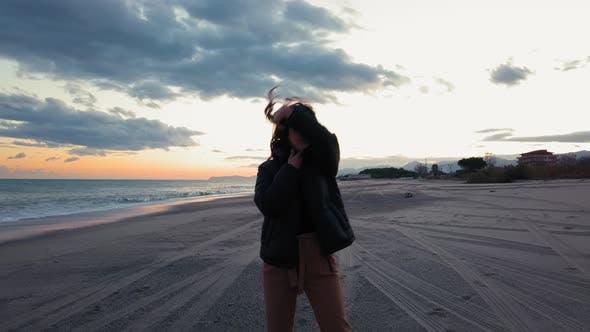 Girl is dancing on the beach near the ocean